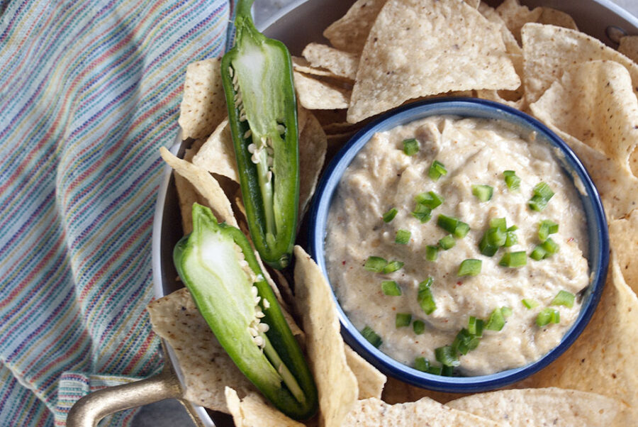 chicken enchilada dip served in a blue bowl with jalapenos and tortilla chips