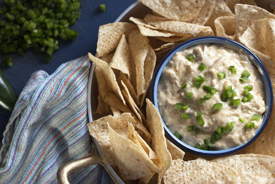 chicken enchilada dip served in a blue bowl with tortilla chips