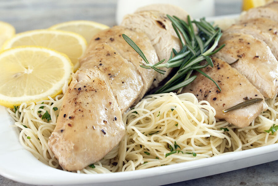Lemon chicken with fresh rosemary and lemon slices over a bed of pasta.