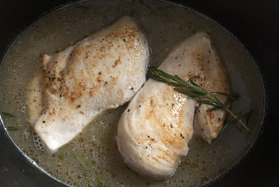 Lemon chicken cooking in the slow cooker with rosemary
