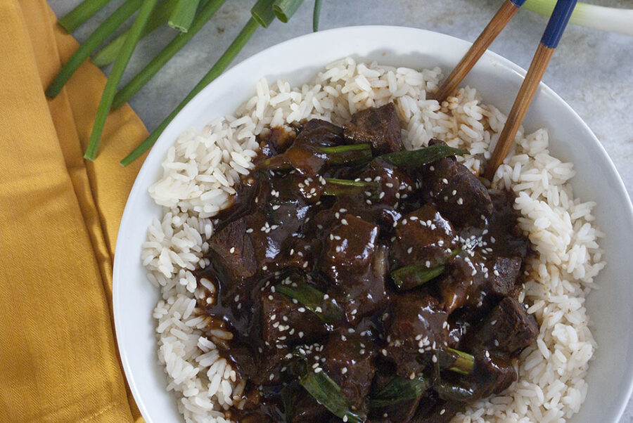 Slow cooker Mongolian beef on a bed of white rice with scallions next to it