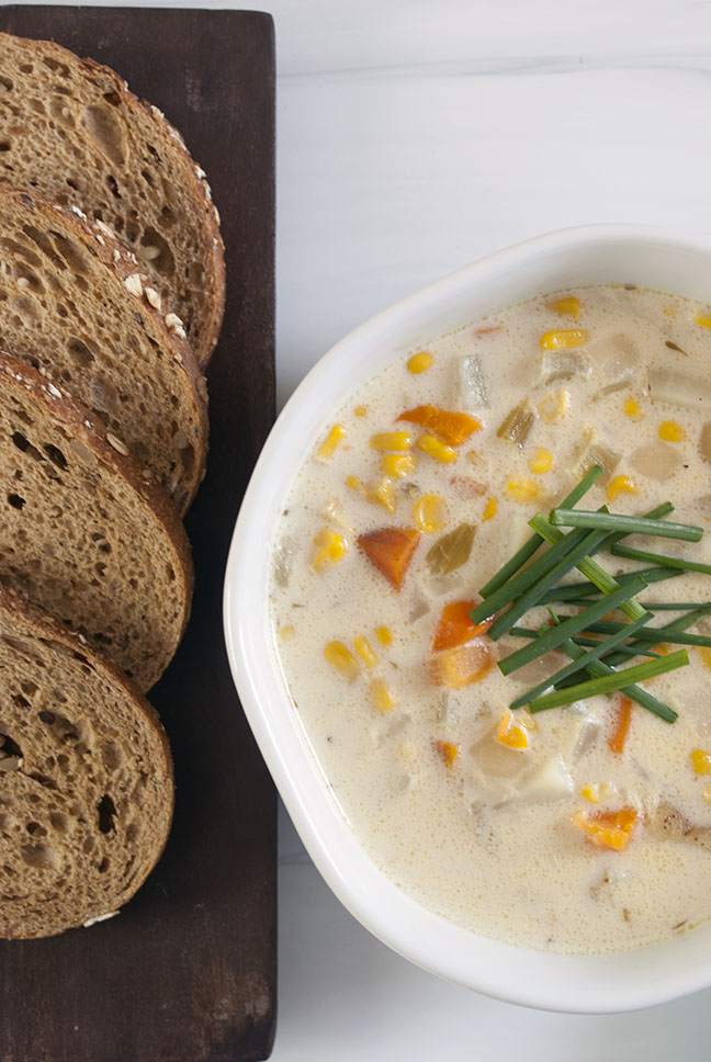a bowl of corn chowder served with slices of bread