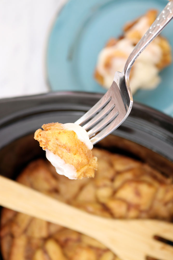 taking a bite of crock pot cinnamon rolls with a fork.