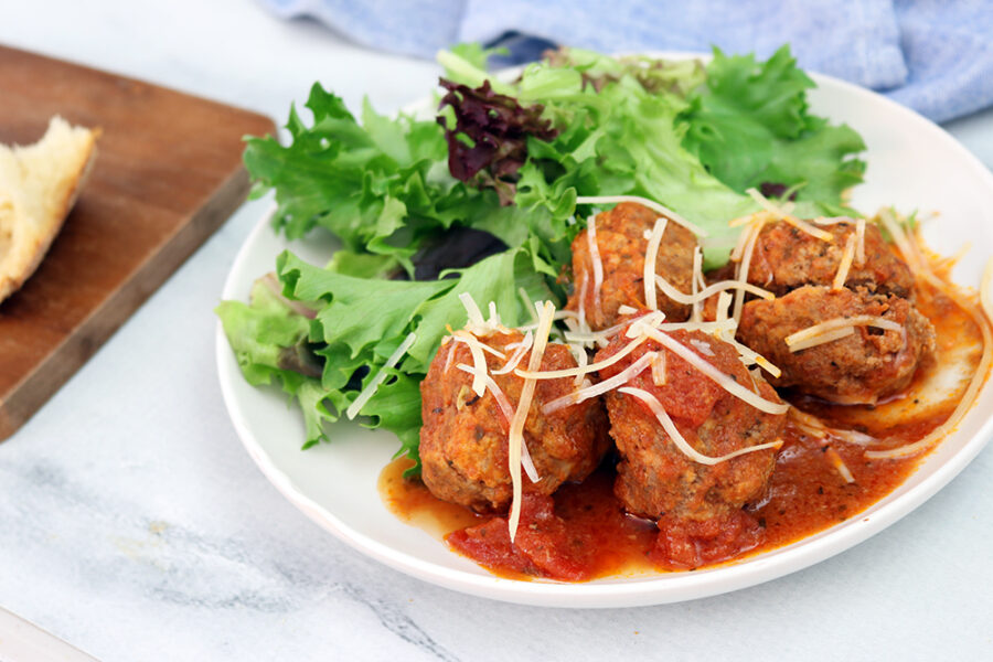 Crockpot meatballs served on a white plate with spring salad and shredded parmesan cheese